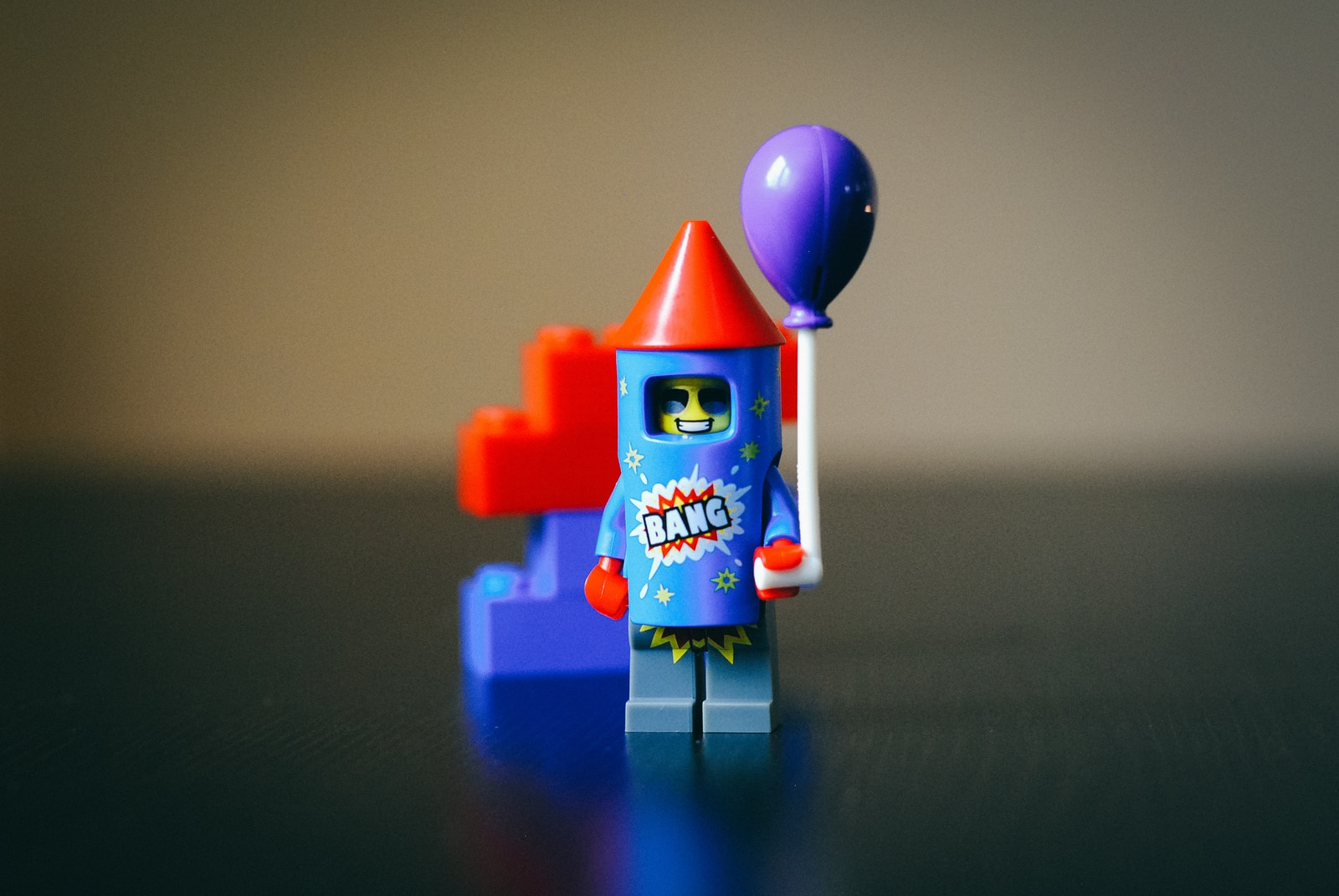 teal, red, and purple LEGO plastic firecracker toy in focus photography